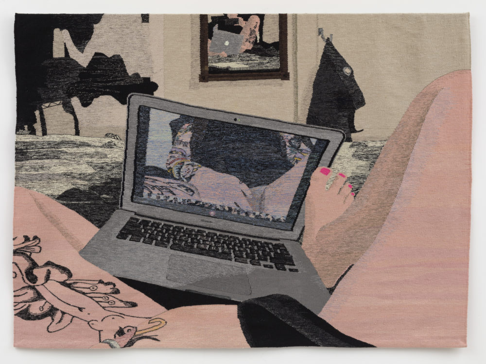 Legs spread in the foreground with a hand at the person's crotch in front of a laptop with the image reflecting back in the screen.