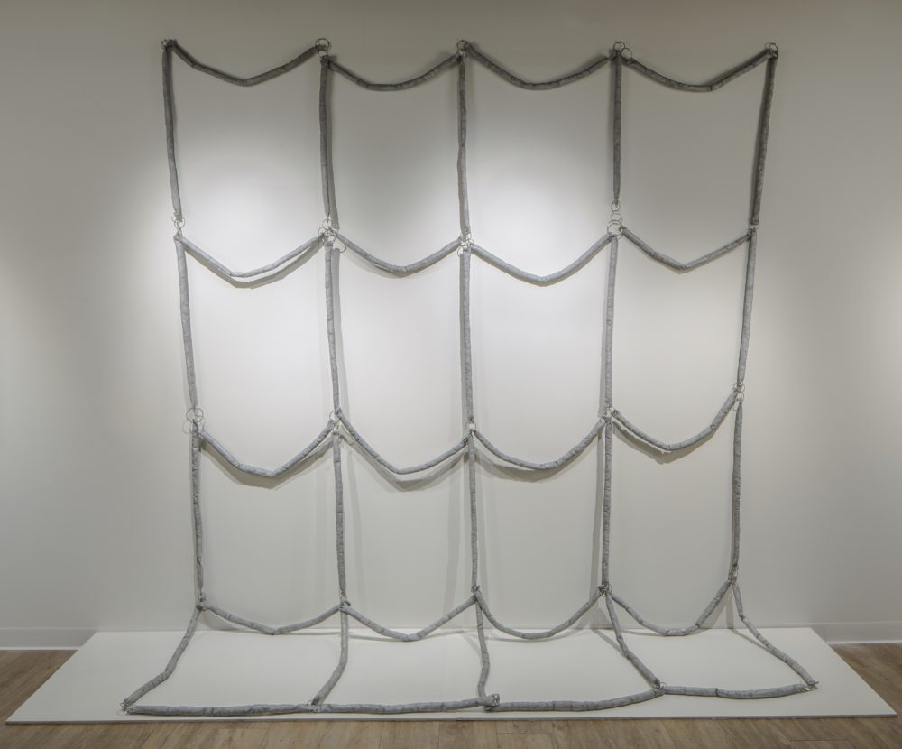 Soft abstract grid sculpture hanging on a wall and resting on the floor.