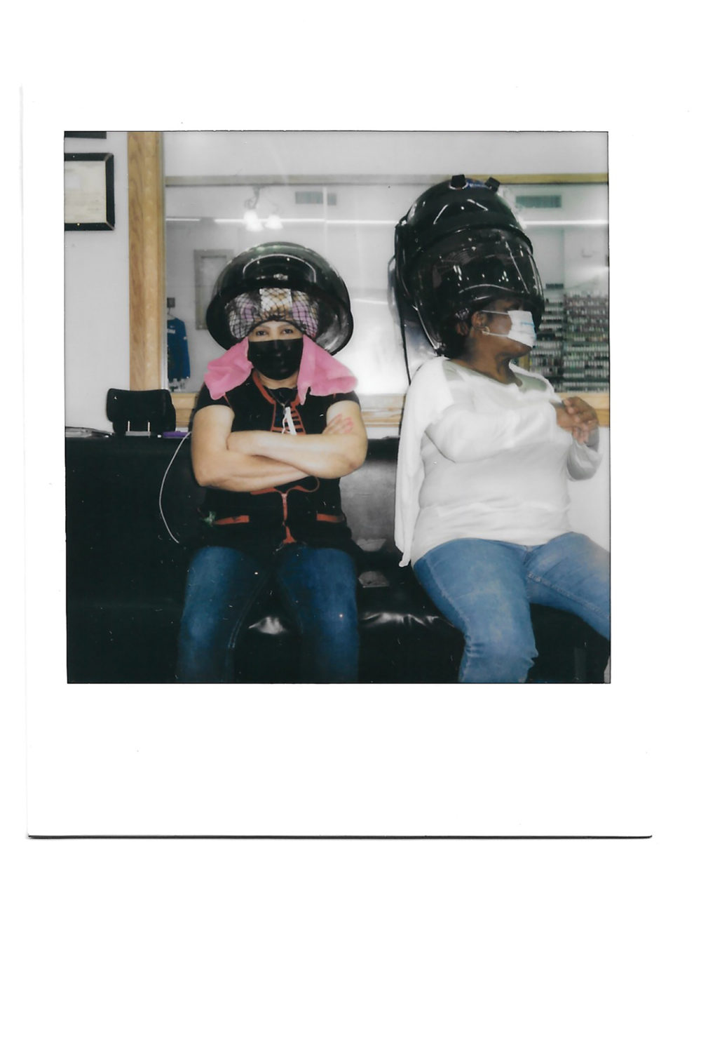Two people sit in a salon underneath a hair dryer