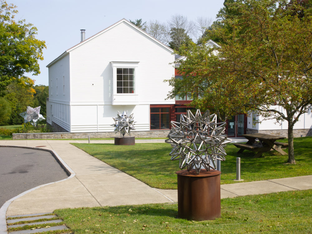 Façade of The Aldrich Contemporary Art Museum with three star sculptures on the grounds.