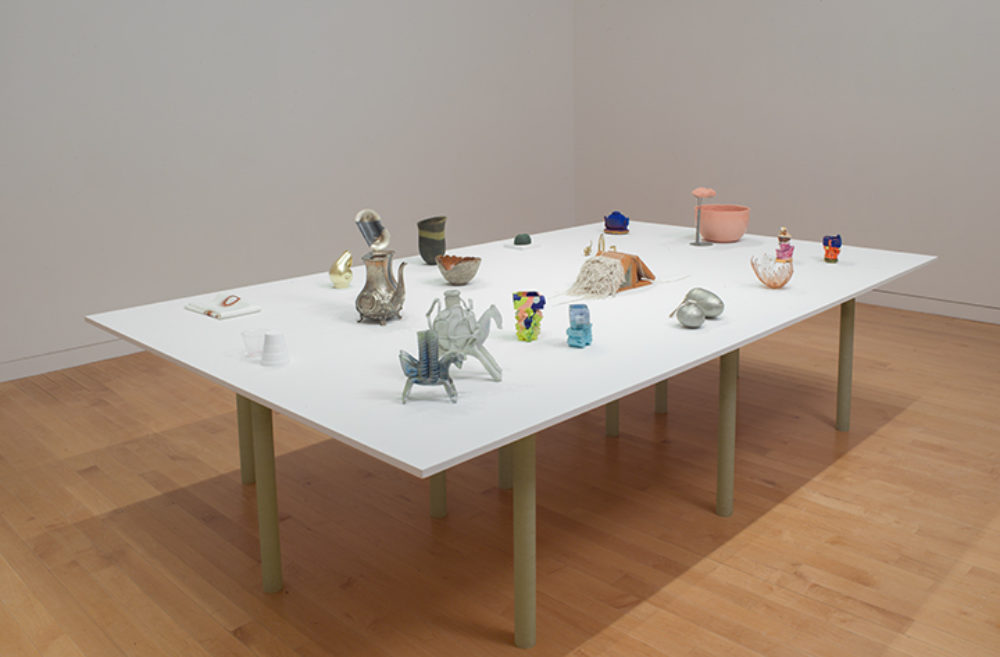 Small sculptural objects sit on a white table