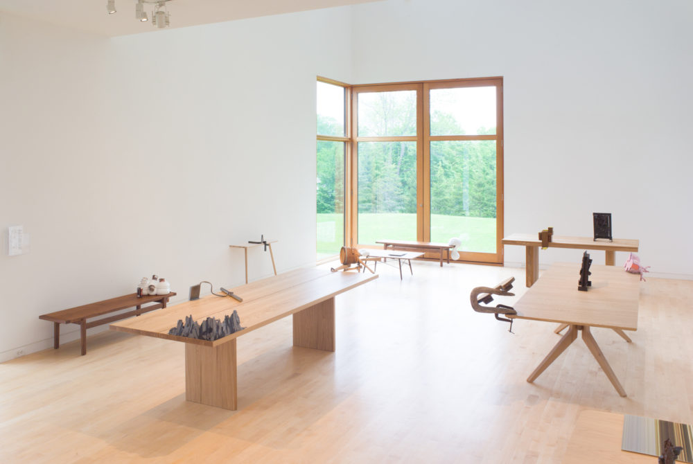 Small objects sit on tables in gallery