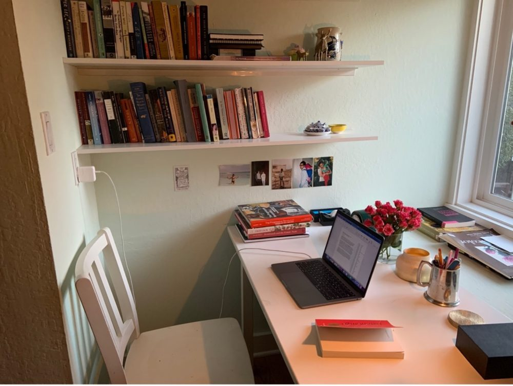 Laptop sits open on a desk with a bookshelf in the background