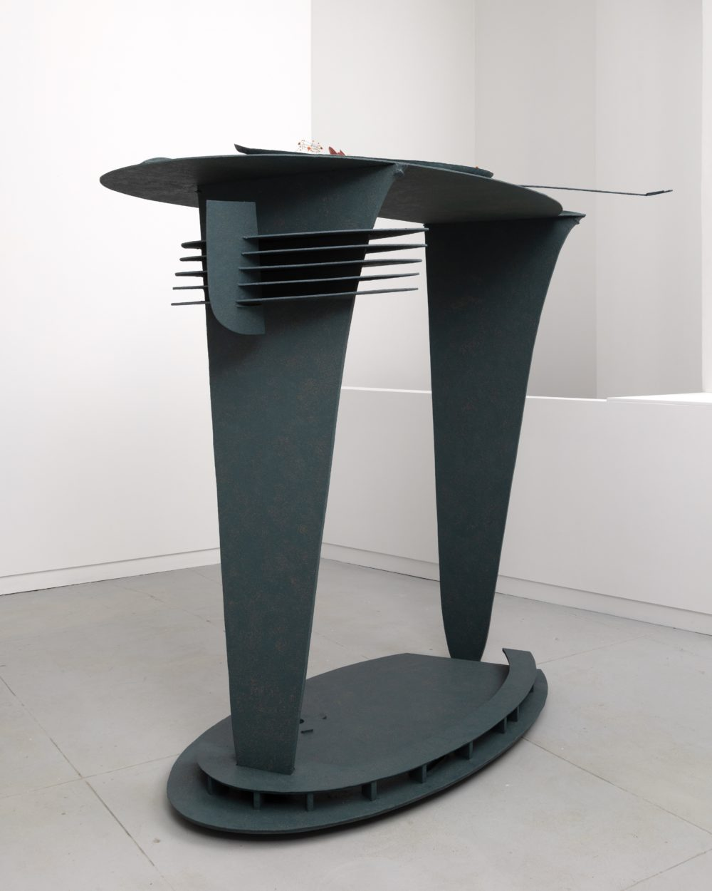 Dark gray sculpture with two legs and an oval base with a flat looking top.