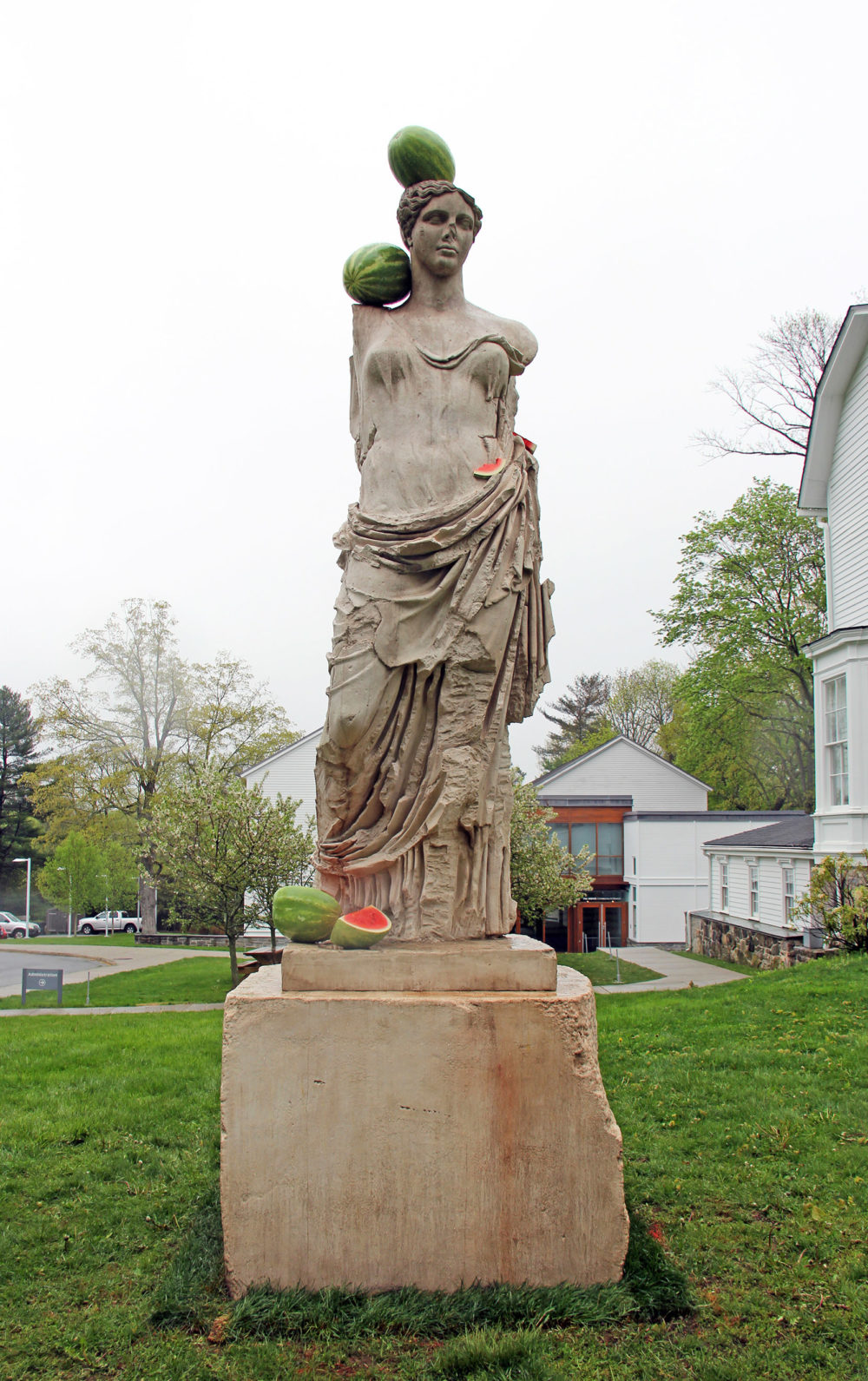 Greek statue of Hera with watermelons resting on stone figure