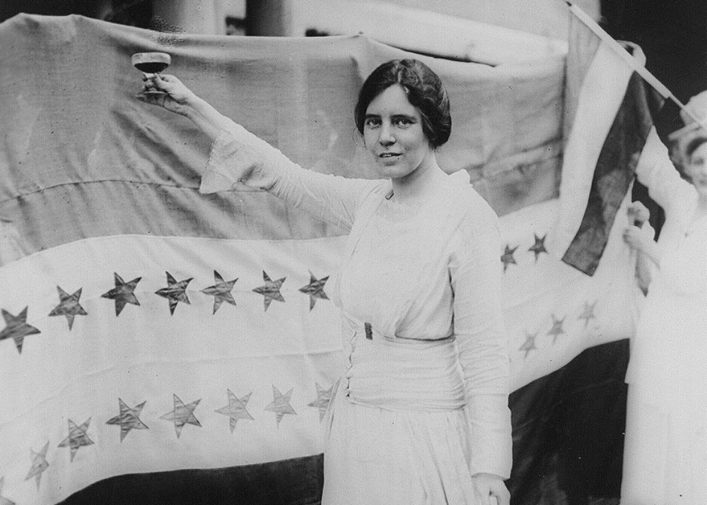 Person in white dress holds a flag with stars on it