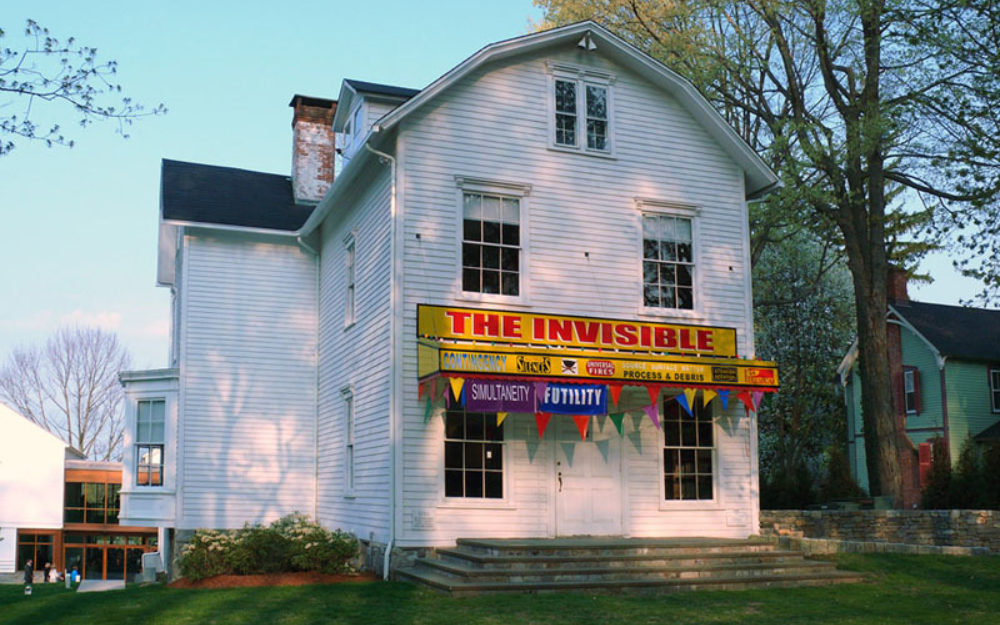 """Image of The Aldrich's Old Hundred admin building with a yellow and red banner reading, """"The Invisible"""""""