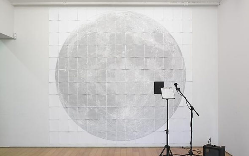 Microphone stands in front of an image of the moon