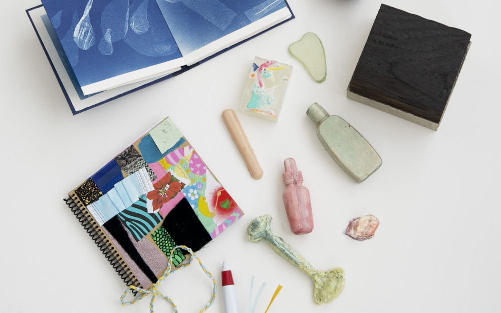 The art contents of the Aldrich Care Box featuring two artists' books and small sculptures.