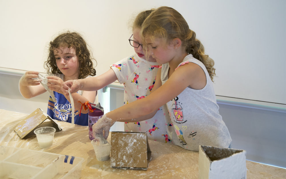Three children work on art projects
