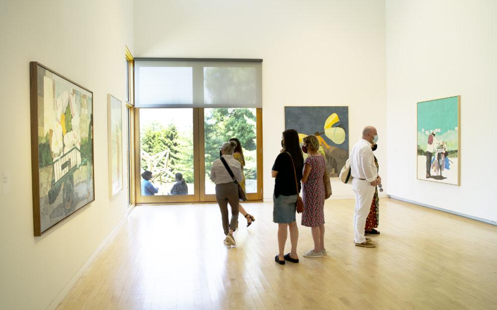 Visitors looking at Hugo McCloud paintings in gallery