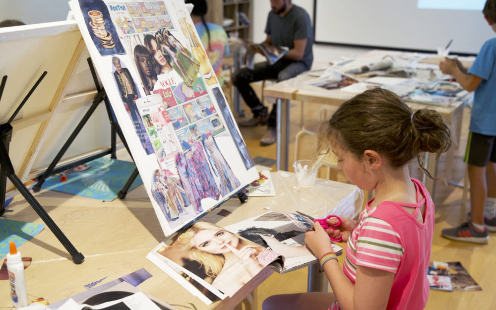 A child working on a collage on a canvas
