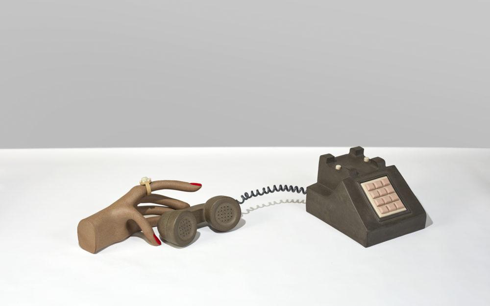 A sculpture of a hand holding a phone
