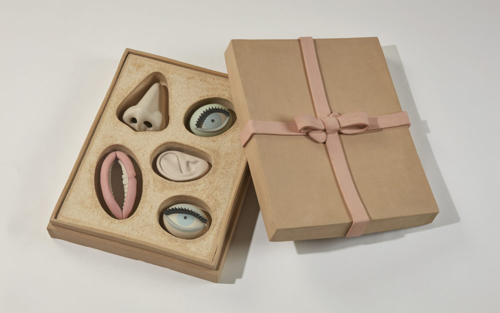 A gift box with small, sculptural works of a nose, two eyes, an ear, and a mouth