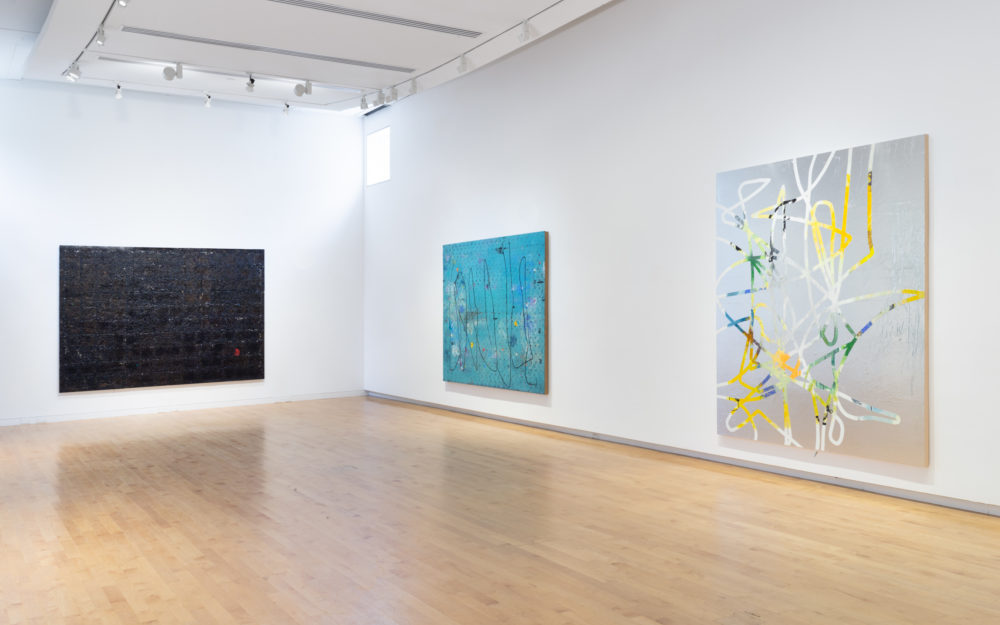 Three canvas works on white gallery walls