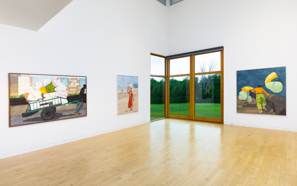 Three large canvas works on white gallery walls with a large window in the background