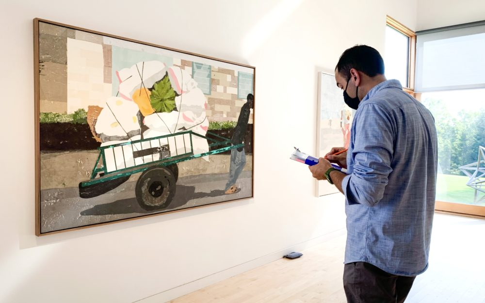 A person looks at a painting in the gallery