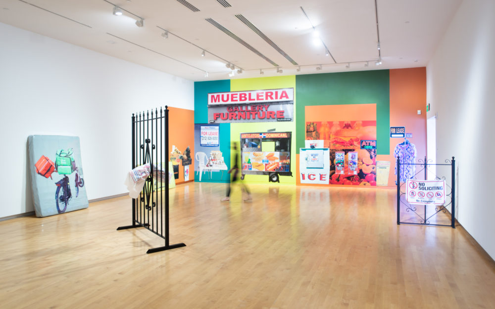 Gallery with two large metal gate sculptures and a colorful wall mural