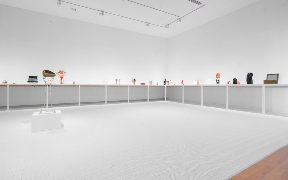Small sculptural objects on shelf in white room