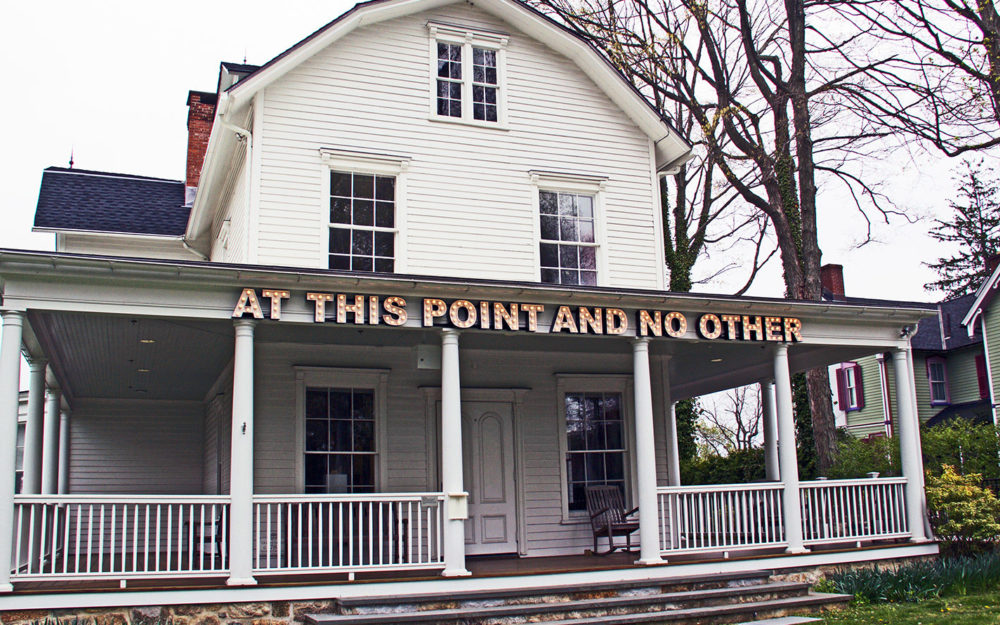 """White building with letters reading """"At This Point and No Other,"""" on front porch"""