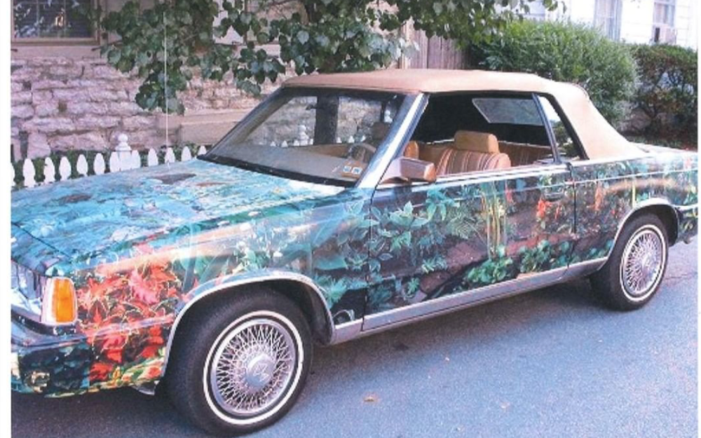 1985 Chrysler LeBaron decorated with leaves of various colors