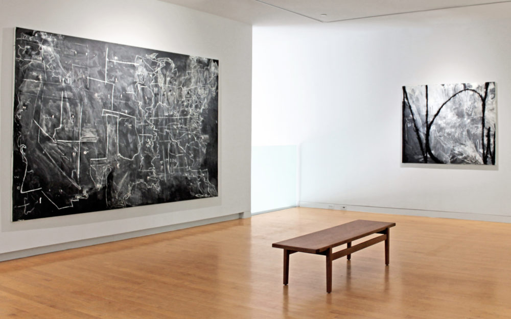 Install view of a gallery with a painting of an abstract map of the United States to the left, a bench in the center and a smaller abstract work to the right.
