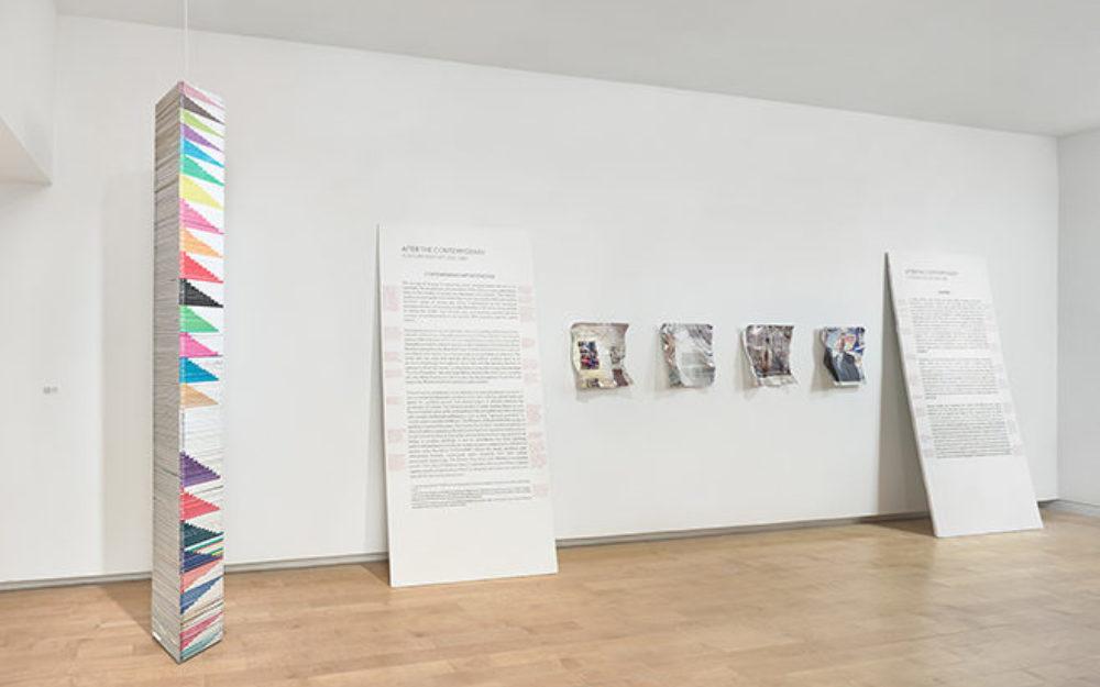 Works by artist William Powhida rest against gallery walls