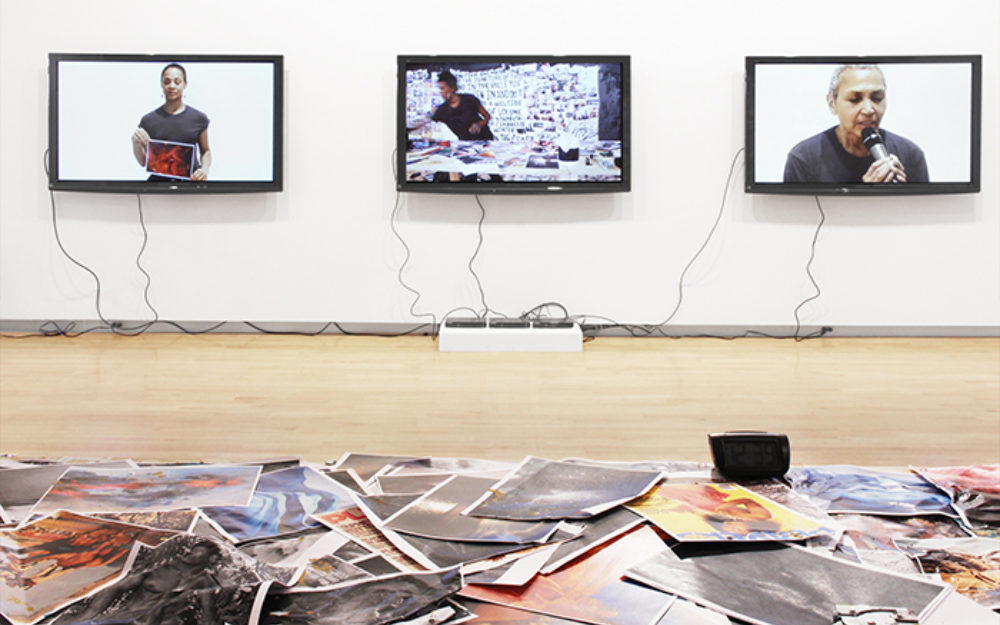 Three screens on a white gallery wall