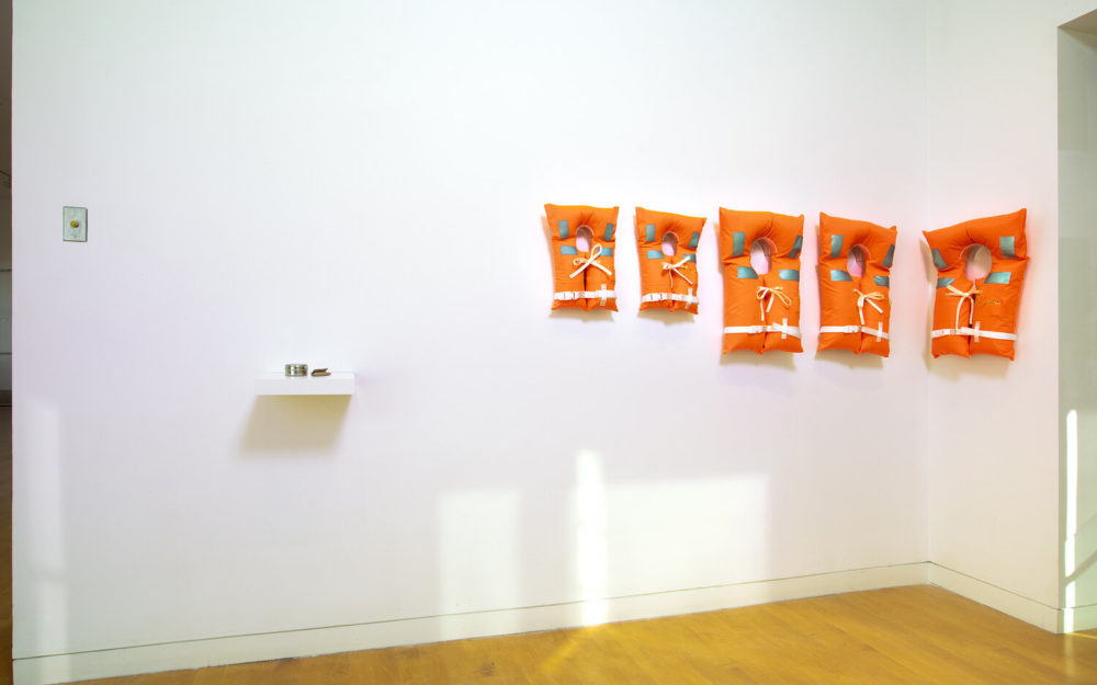 Five orange life jackets on gallery wall