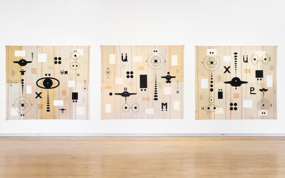 Three large-scale unstretched paintings with similar dark motifs against cream colored background hung together on a wall.