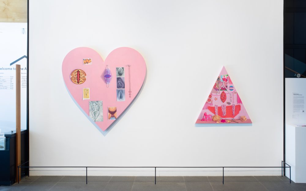 Two large pink canvas works on a white wall