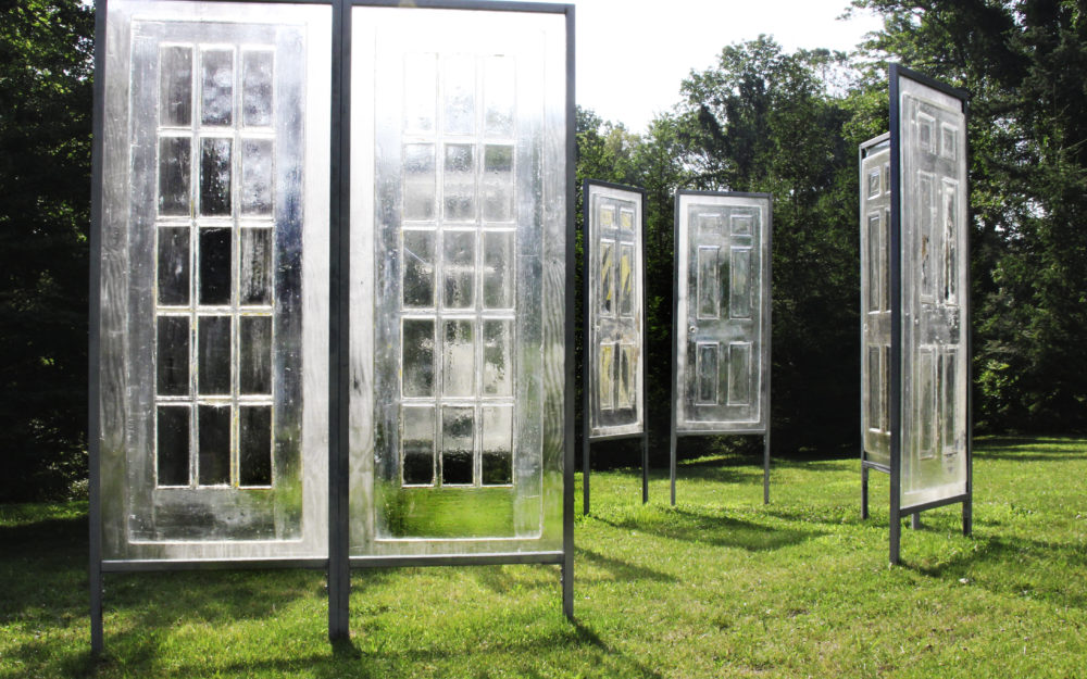 Clear window panels stand up right on a green lawn