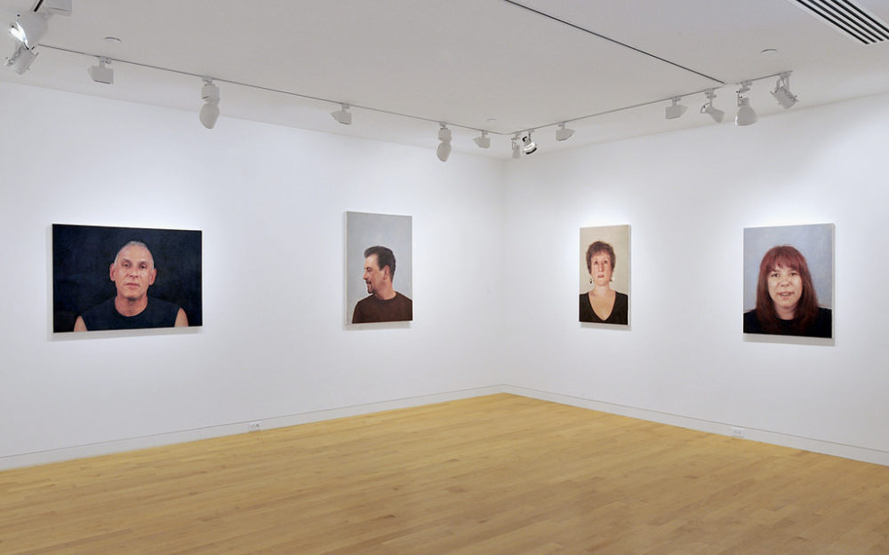 Four portraits hang on the gallery walls