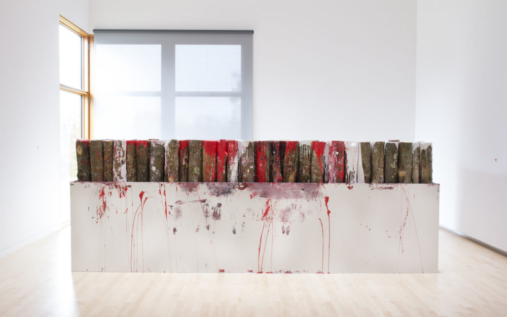 Wood covered in red paint placed in a white sculpture
