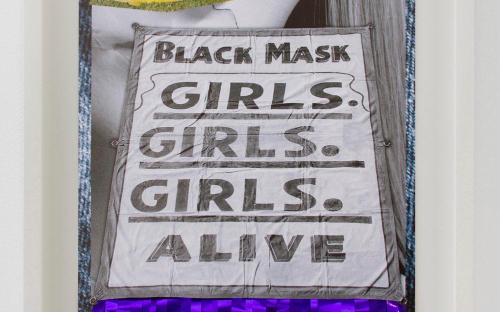 """Banner reading """"Black mask, Girls. Girls. Girls. Alive,"""" in gray font"""