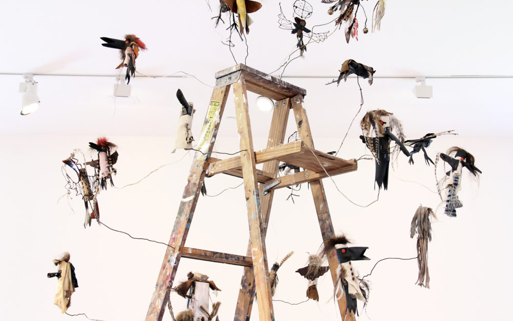 Small figurative sculptures surrounding the top of a wooden ladder