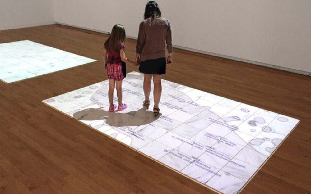 Two visitors look down at a work of art projected on the gallery floor