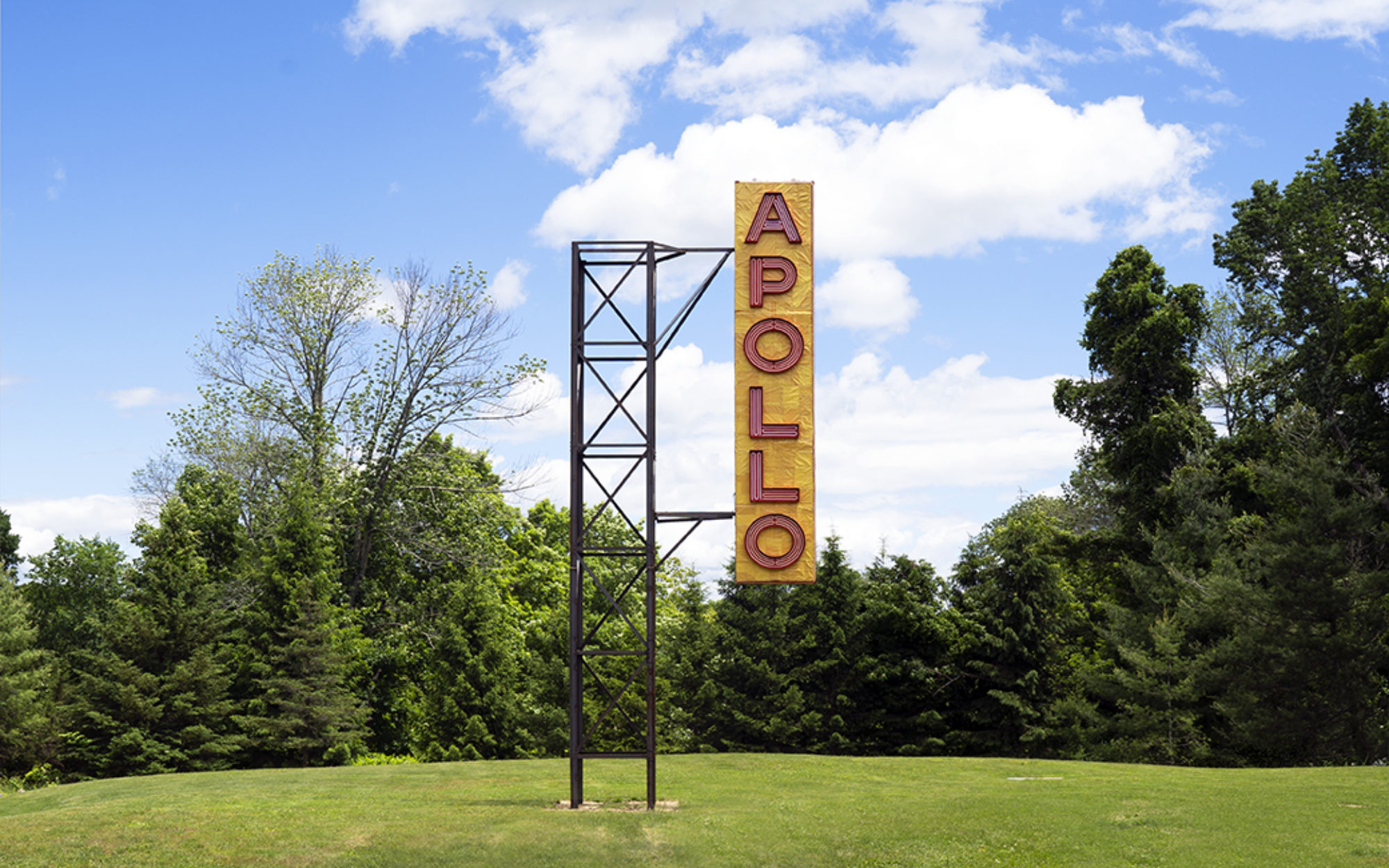 Large yellow sign with red letters reading APOLLO