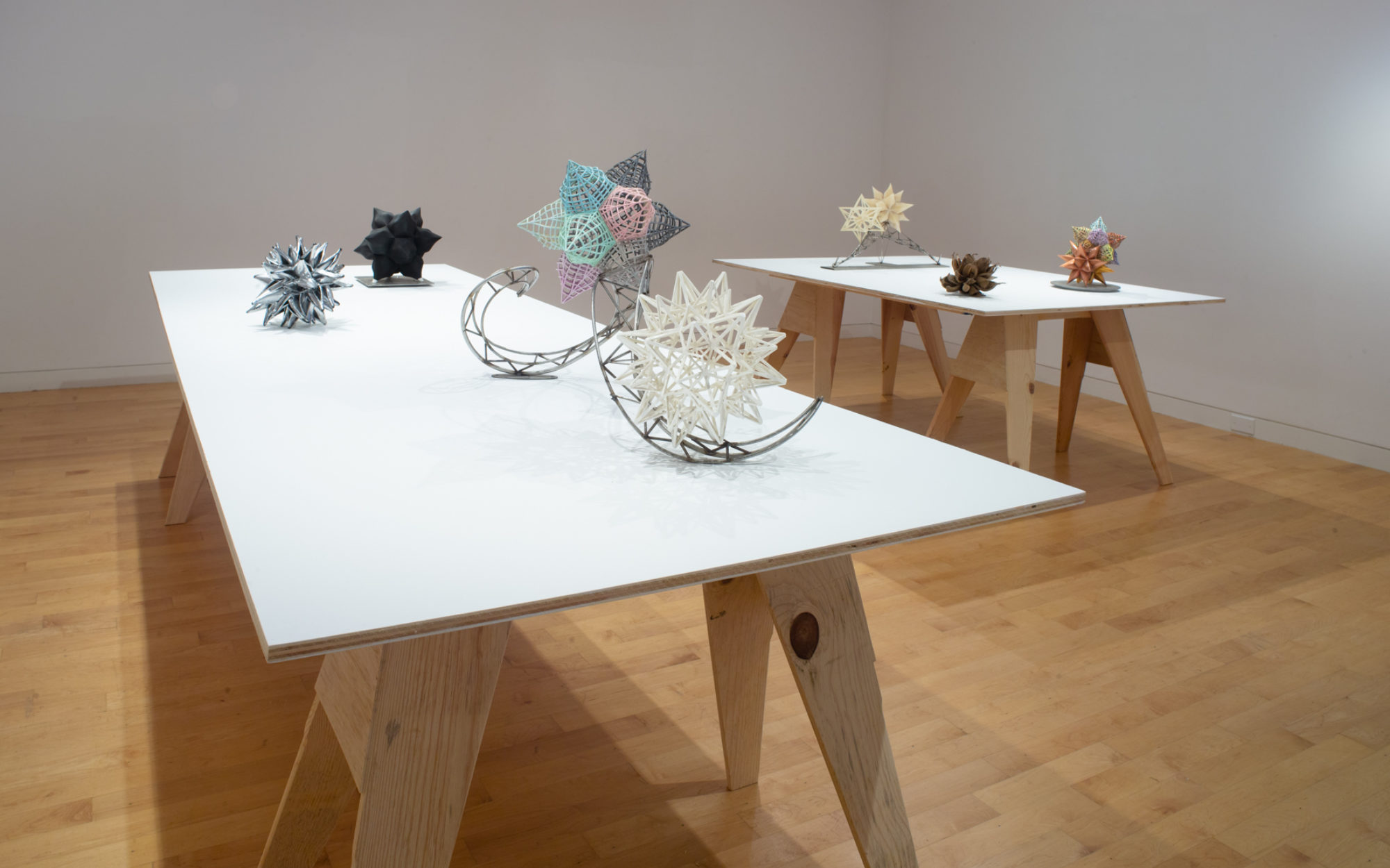 Small scale maquettes for larger sculptures by Frank Stella on tables with white surfaces.