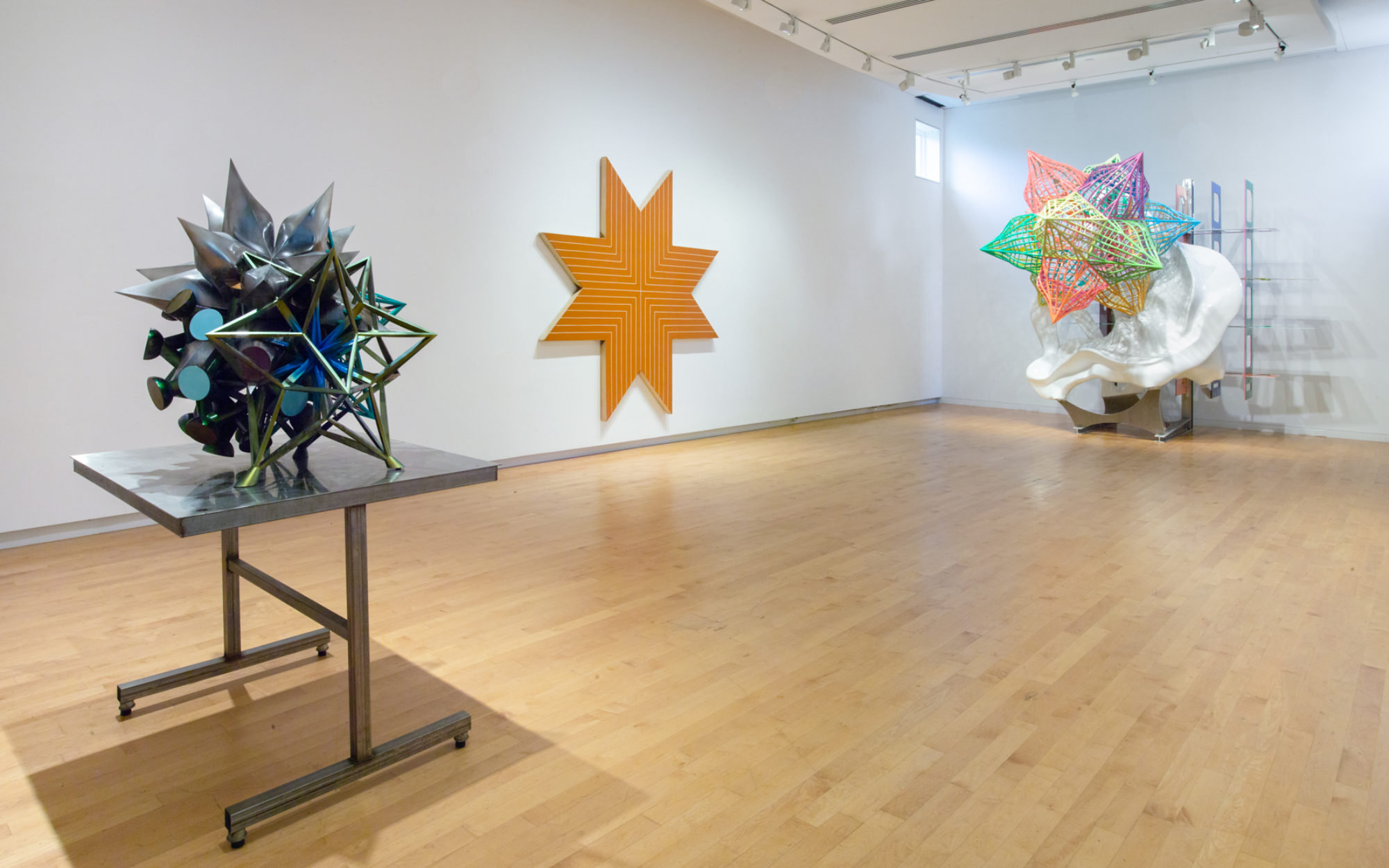 Photo of gallery with a small sculpture to left, a large star-shaped painting at center, and a large sculpture featuring a colorful star to the right.