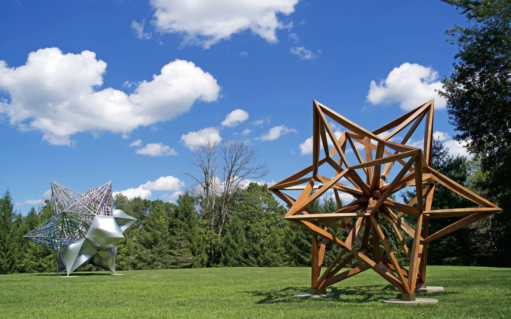 Two large scale star shaped sculptures installed on the grass in the Museum's Sculpture Garden.