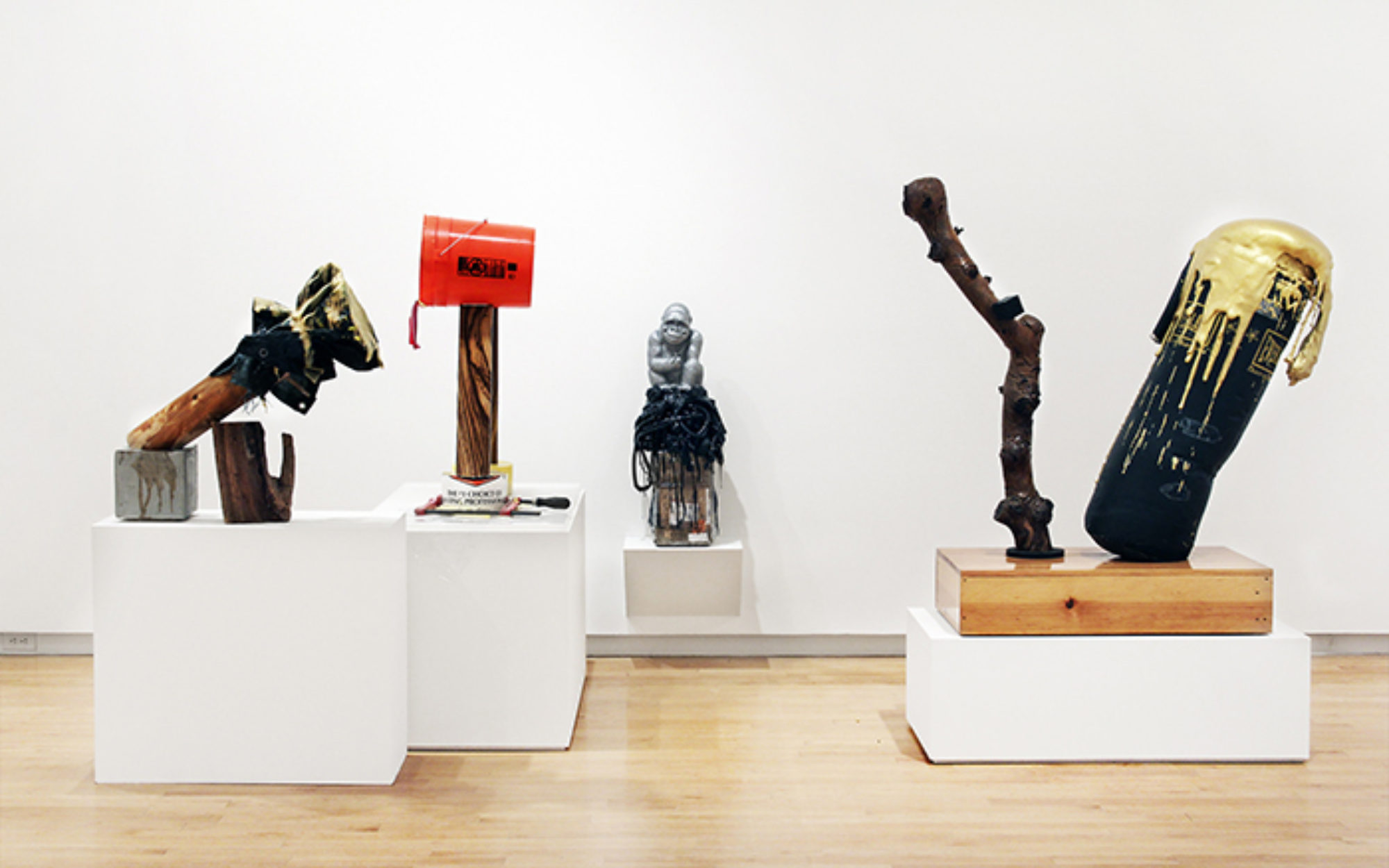 Four sculptural works sit on white platforms in gallery