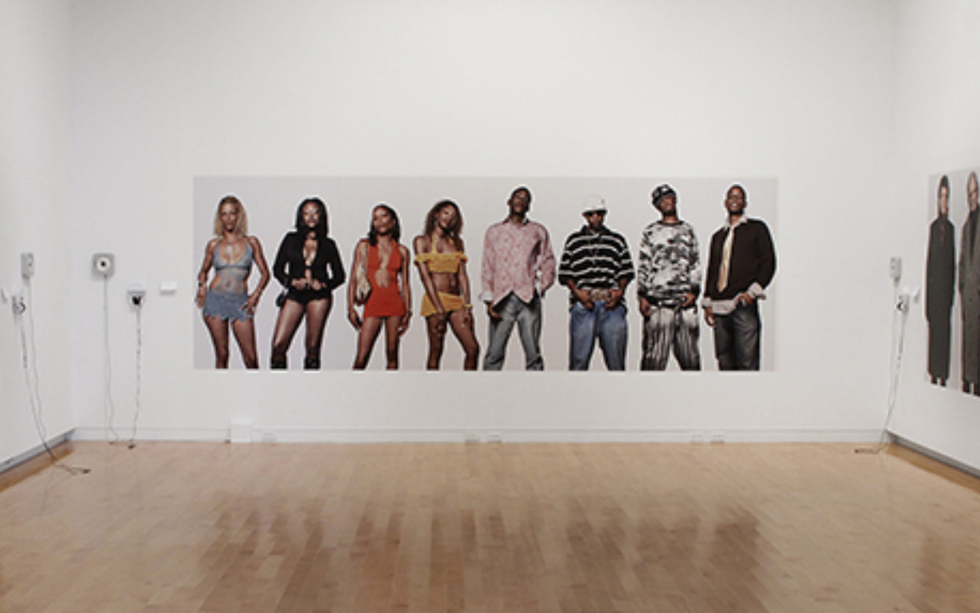 A photo of eight individuals on a white gallery wall