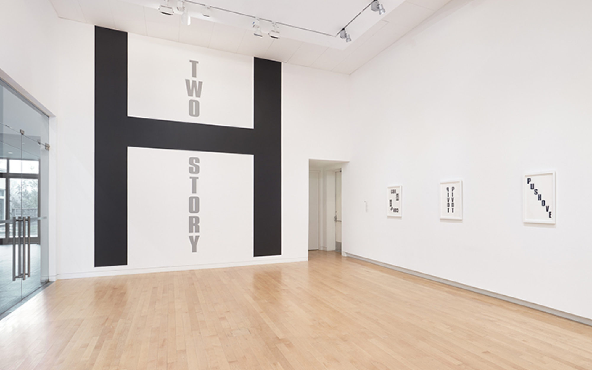 """Large black H on gallery wall with the words """"Two Story,"""" in gray"""