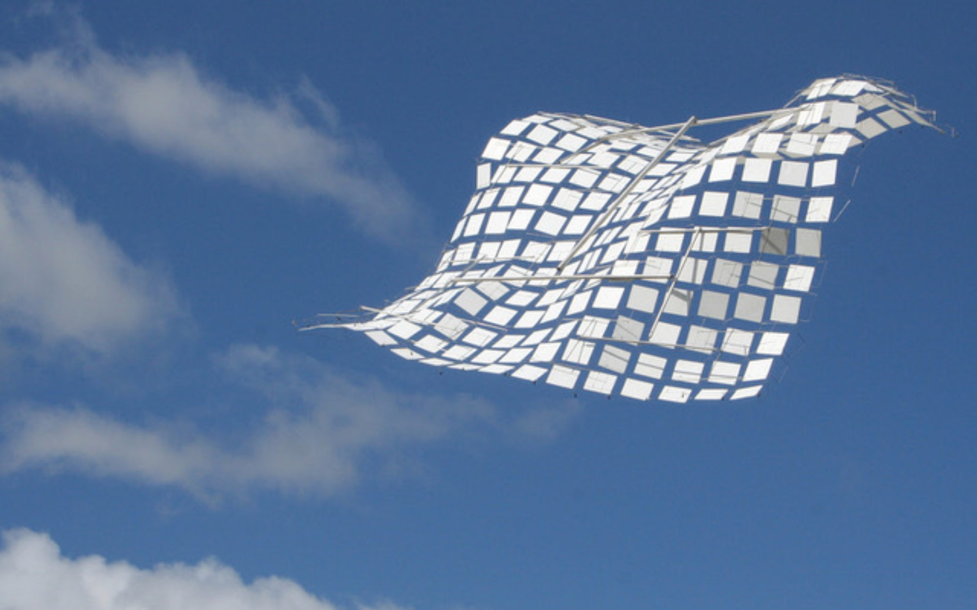 Sculpture of white squares linked together against a blue sky.
