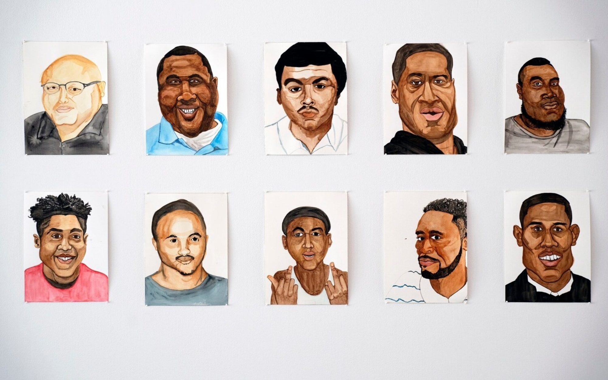 Detail of watercolor portraits against white wall
