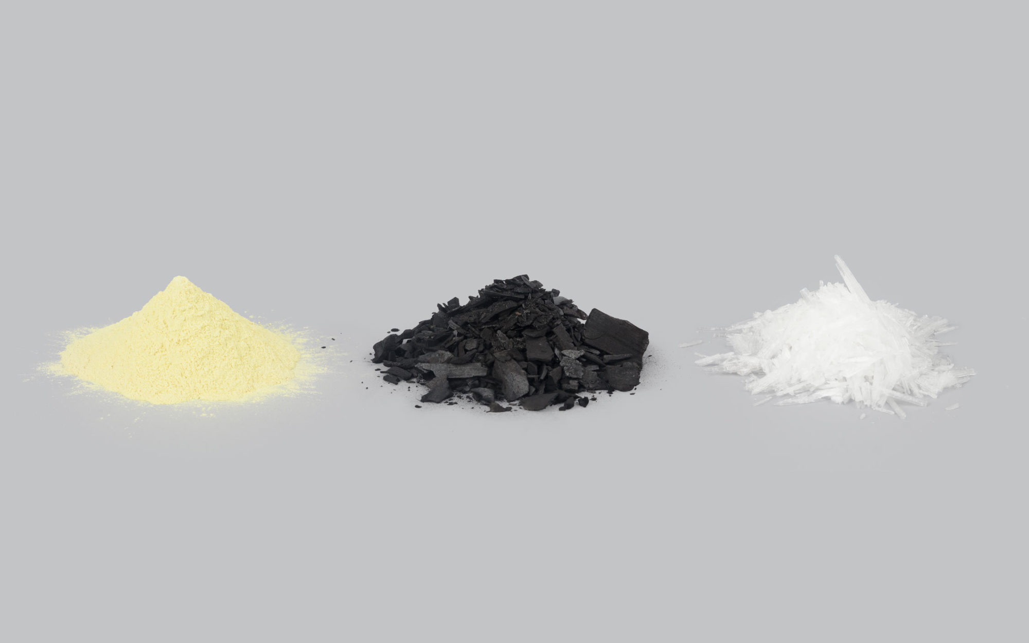 A yellow pile of sulfur, a black pile of charcoal, and a white pile of saltpeter against a gray background