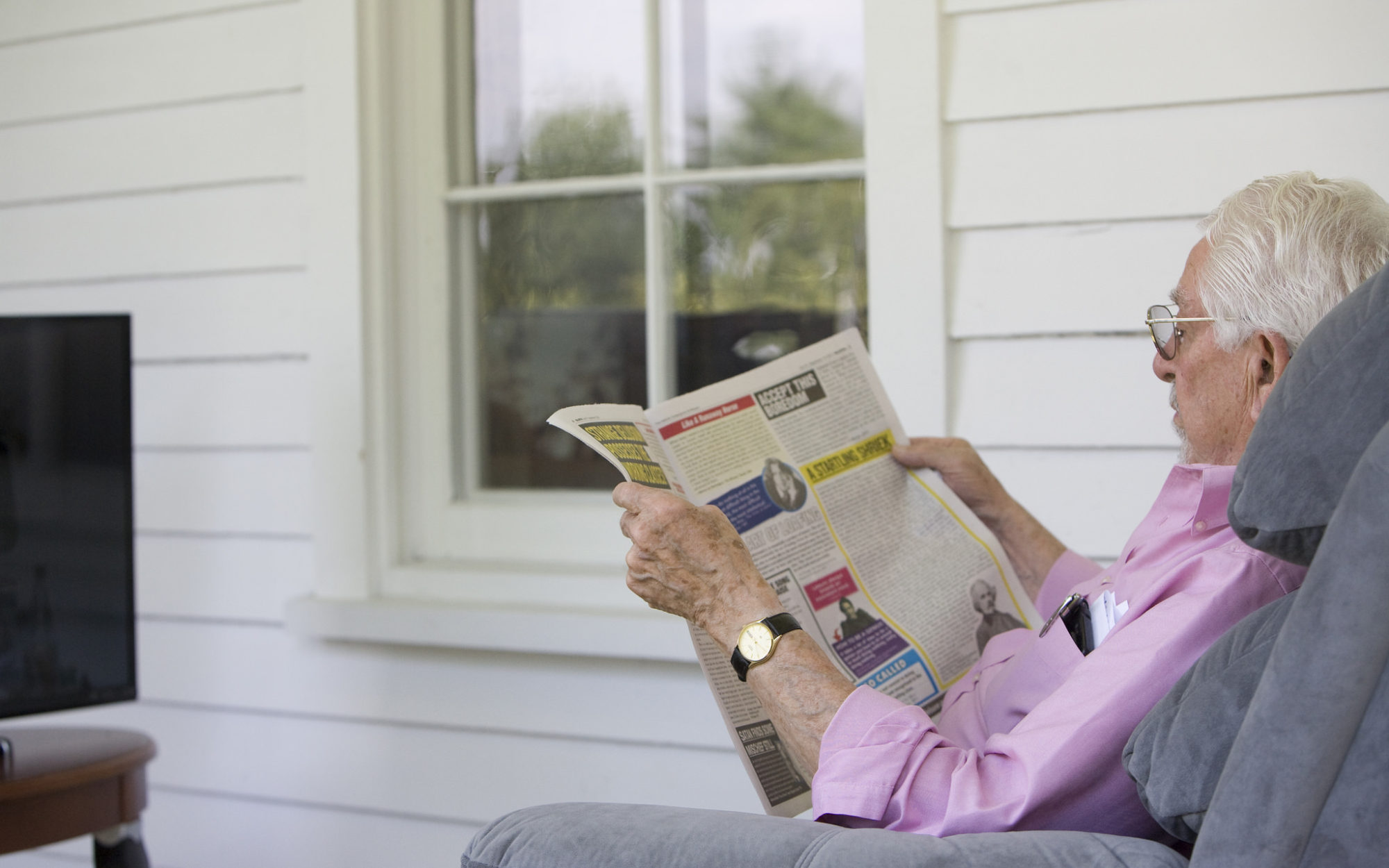 Individual sits in a recliner and reads the newspaper