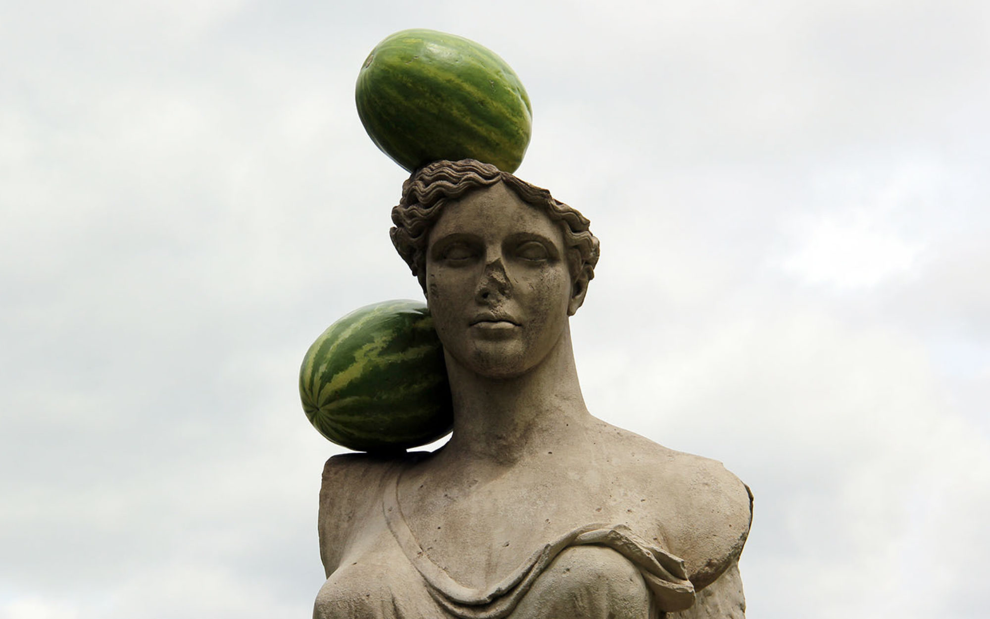 Stone sculpture with two watermelons resting on head