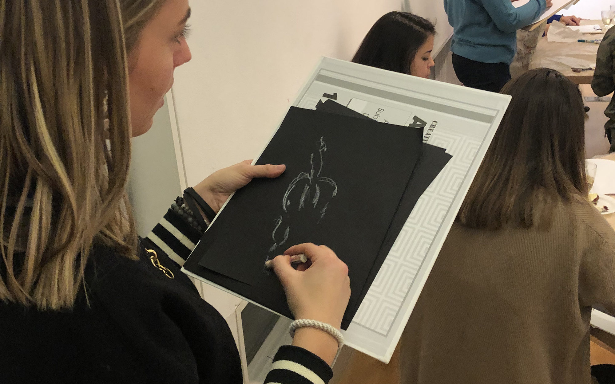Person draws a sketch on a black piece of paper